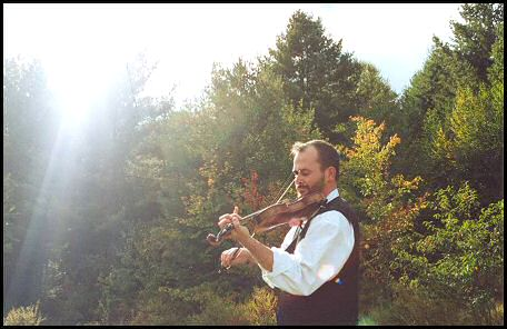 Photo of Brendan Taaffe playing the fiddle outdoors.